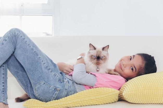 Menina que joga com o gato no sofá em casa, conceito da amizade.