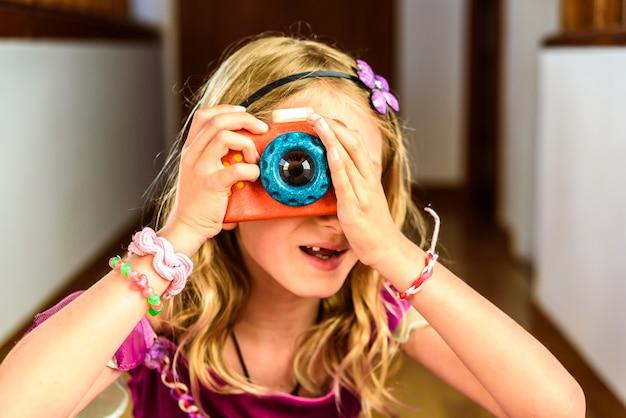 Menina que joga com um brinquedo colorido da câmera da foto feito da madeira.