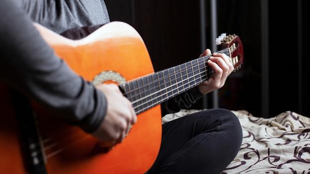Menina que joga um close da guitarra acústica de seis cordas. aulas de instrumentos musicais.