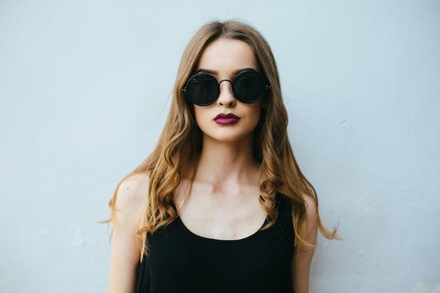 Menina que levanta com óculos de sol