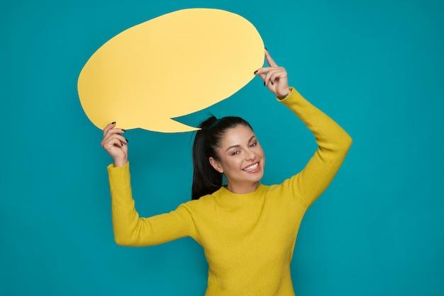 Menina que mantém despesas gerais amarelas da bolha do discurso, sorrindo.