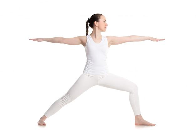 Menina que mostra o equilíbrio na aula de ioga Foto gratuita