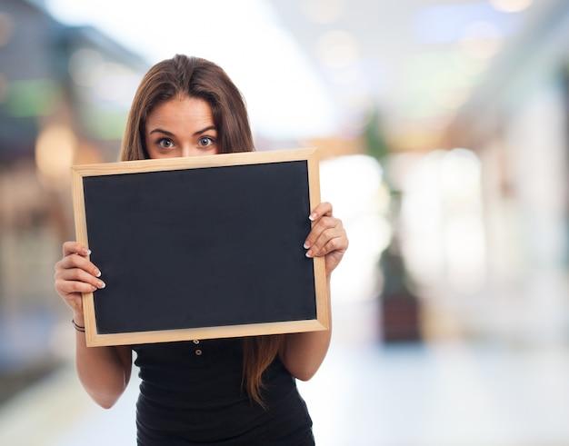 Menina que mostra um pequeno quadro-negro com fundo borrado