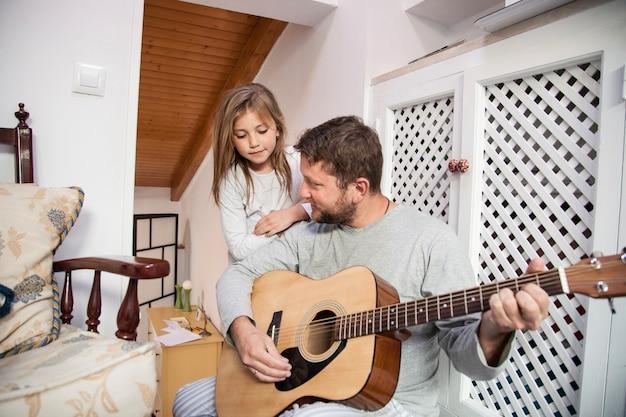 Menina que olha seu pai ao jogar a guitarra