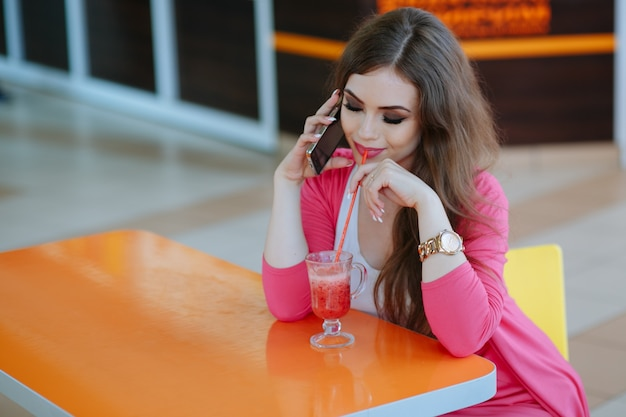 Menina que olha seu refrigerante enquanto fala ao telefone