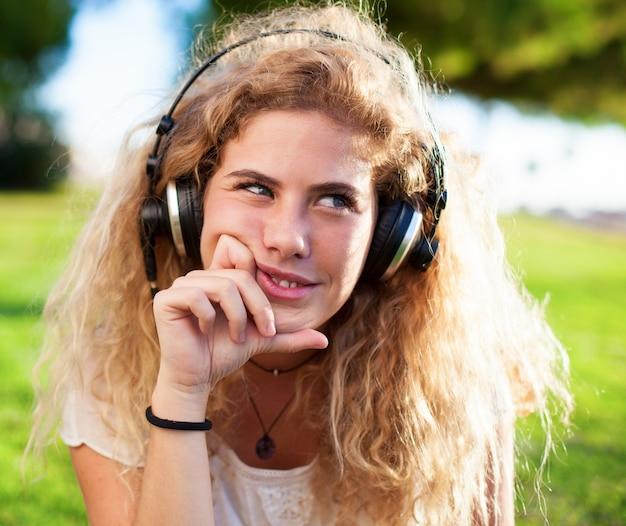 Menina que pensa ao ouvir música ao ar livre