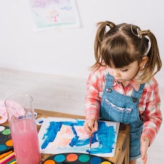 Menina que pinta com aquarelle na mesa de madeira