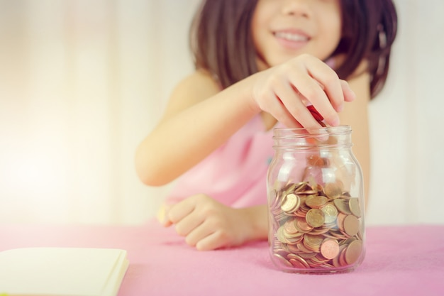 Menina que põe uma moeda em um mealheiro, conceito de salvamento do dinheiro da criança.