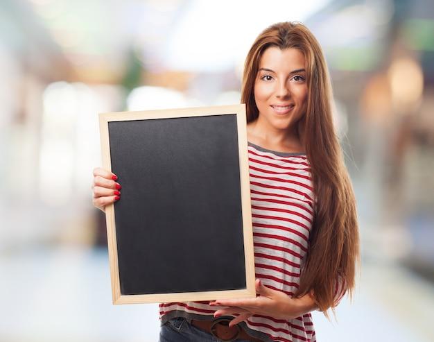 Menina que prende o quadro-negro no frame de madeira