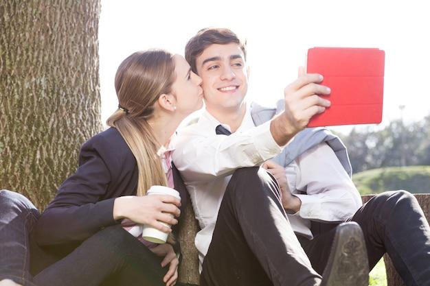Menina que prende um café e beijando a bochecha de seu namorado