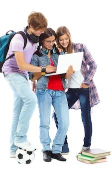 Menina que prende um portátil com seus amigos