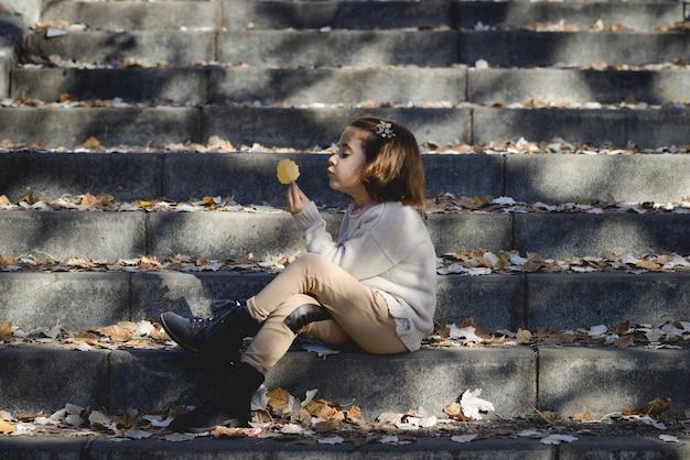 Menina que prende uma folha sentada na escada