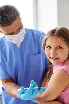 Menina que recebe a injeção no braço