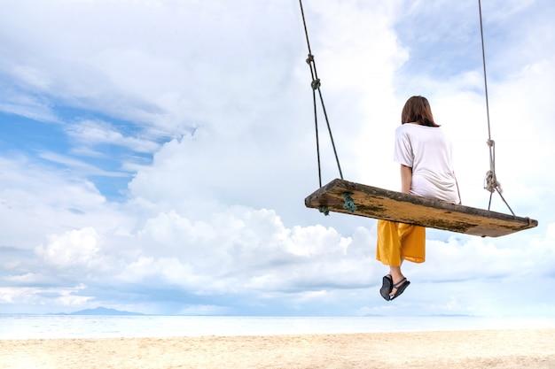 Menina que relaxa no balanço na praia tropical da areia com fundo do céu azul e do mar.
