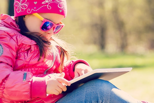 Menina que senta-se na grama e que joga o pc da tabuleta, tonificando a foto.