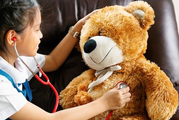 Menina que sorri e que joga o doutor com urso marrom e estetoscópio. kid e cuidados de saúde