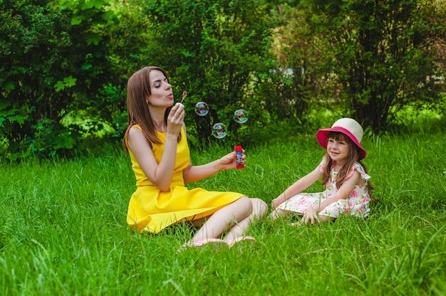 Menina que sorri enquanto sua mãe funde bolhas de sabão