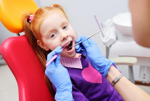 Menina que sorri na cadeira dental vermelha. o dentista examina os dentes do paciente da criança. dentista pediátrico
