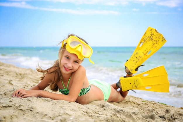 Menina que sunbathing na praia na máscara e nas aletas para o mergulho autónomo.