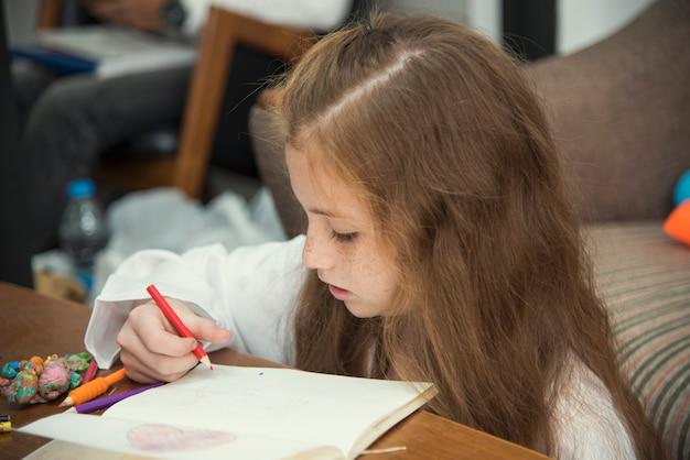 Menina que tira retratos coloridos usando pastéis do lápis na tabela dentro.