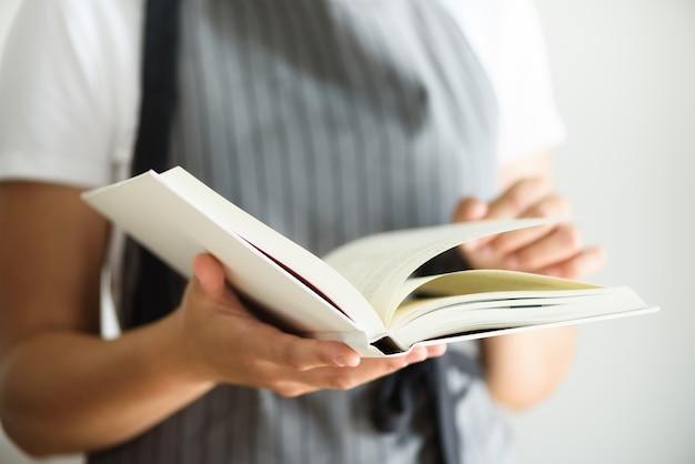 Menina que veste o avental e o livro de leitura cinzentos. conceito de estilo de vida