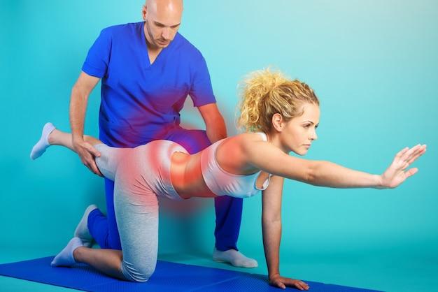 Menina realiza exercícios com um fisioterapeuta. fundo ciano