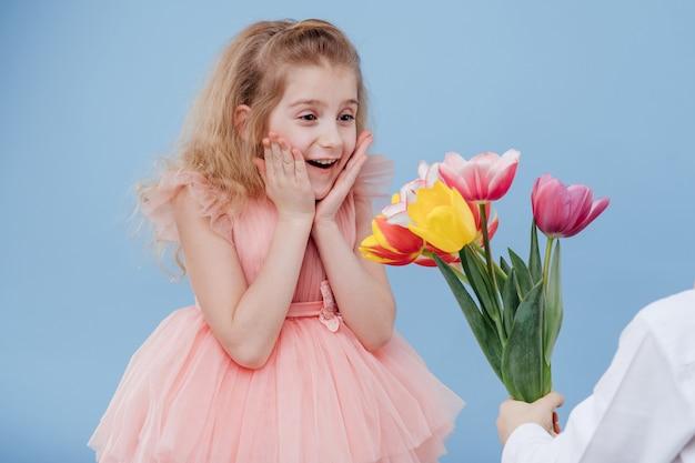 Menina recebe flores, isoladas na parede azul, close-up, duas crianças.