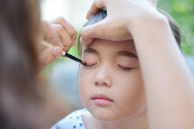 Menina recebendo seu rosto para maquiagem pelo maquiador