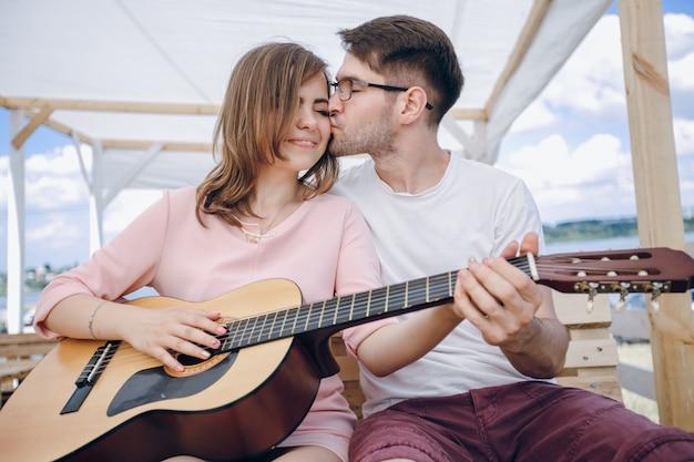 Menina recebendo um beijo, enquanto a tocar guitarra