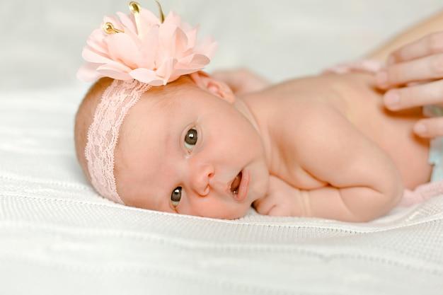 Menina recém-nascida está deitado em sua barriga com uma flor na cabeça e as mãos de sua mãe estão acariciando