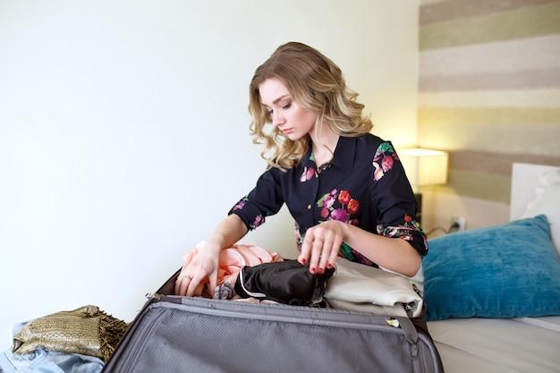 Menina recolhe roupas em uma mala.