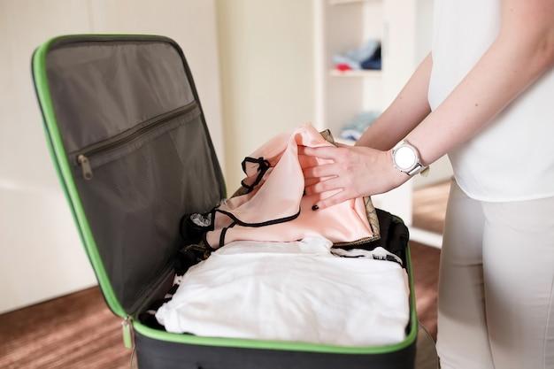 Menina recolhe uma mala em um quarto de hotel.