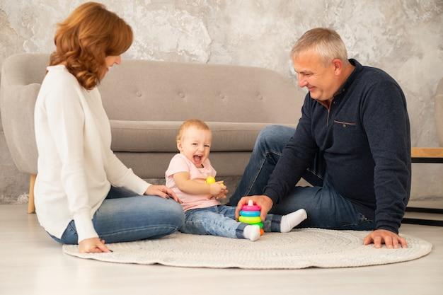 Menina recolhe uma pirâmide com os avós na sala de estar. família passa um tempo juntos em ambientes fechados