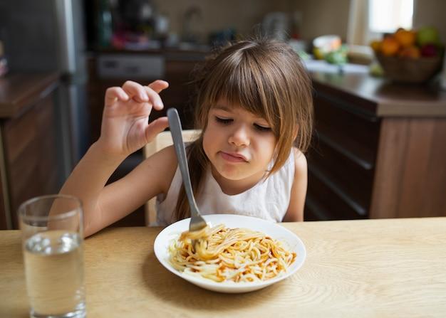 Menina, recusando o prato de massa em casa