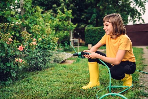 Menina regando flores no jardim