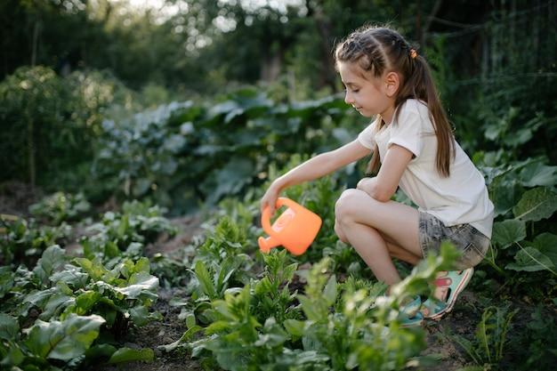 Menina regando o jardim no verão pela manhã