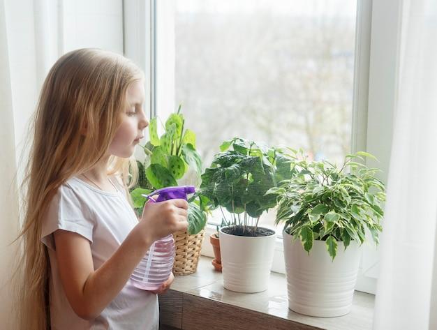 Menina regando plantas domésticas em sua casa