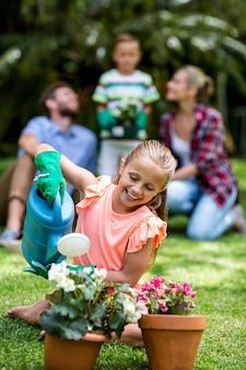 Menina regando vasos de flores no quintal