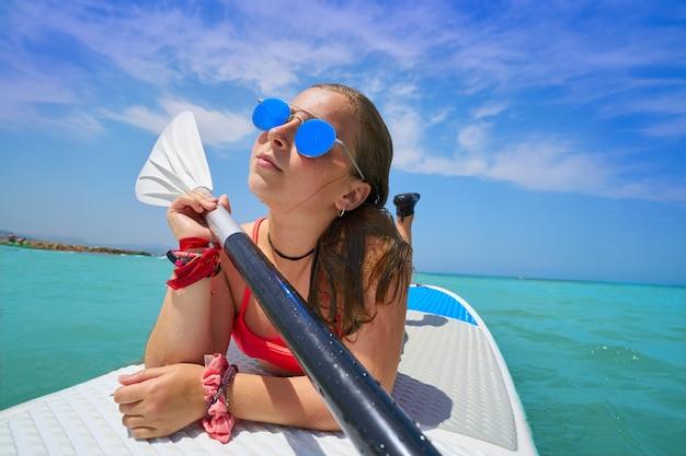 Menina relaxada deitada na prancha de surf paddle