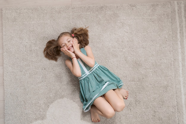 Menina relaxada, deitado no chão dentro de casa e sorrindo