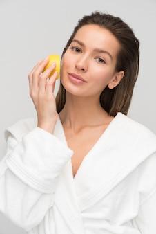 Menina relaxada e encantada cuidando de sua pele do rosto