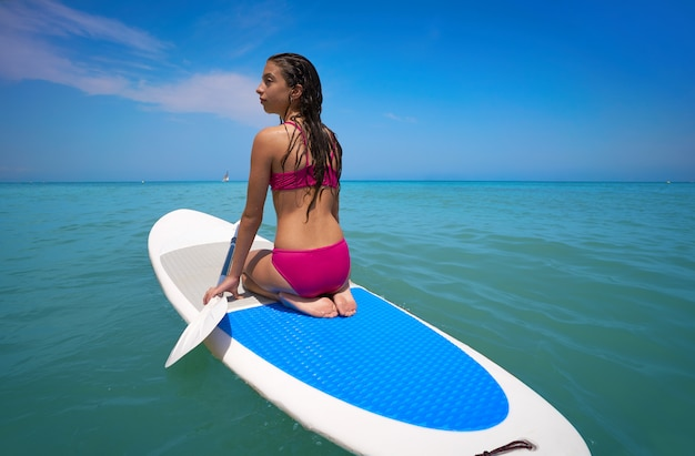 Menina relaxada na prancha de surf paddle