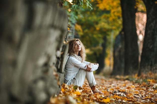 Menina relaxada sentado em folhas secas
