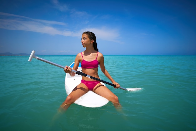Menina relaxada sentado na prancha de surf paddle