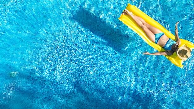 Menina relaxando na piscina, criança nadando no colchão inflável e se divertindo na água, resort tropical de férias, vista aérea do drone de cima