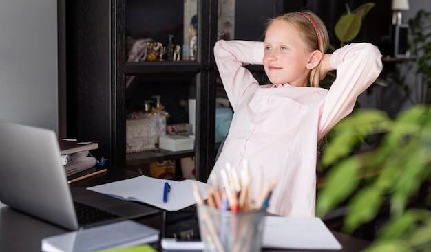 Menina relaxante enquanto faz uma aula on-line
