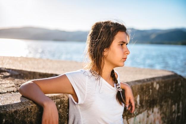 Menina relaxante junto ao rio