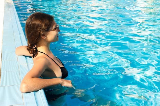 Menina relaxante perto da piscina. férias de verão