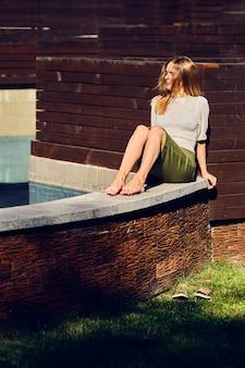 Menina relaxante sob o sol perto da água no dia quente sensual