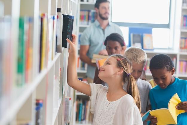 Menina, removendo o livro da estante na biblioteca